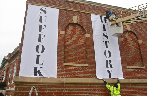 Ryan Egan (top) and Stephen Tang hang the vinyl tarps at Suffolk County Historical Society on Tuesday. (Credit: Barbaraellen Koch)