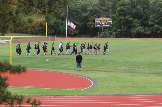 Members of the Shoreham-Wading River football team walk out onto the field during Thursday's vigil. (Credit: Jen Nuzzo)
