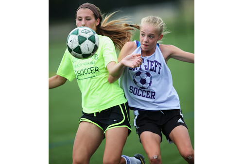 Shoreham-Wading River's Alex Kuhnle, left, and Port Jefferson's Jillian Colucci competing for possession of the ball during a summer league game. (Credit: Garret Meade)