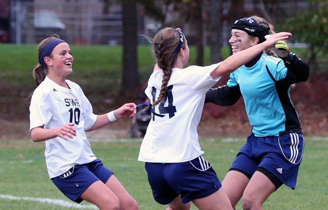 Shoreham-Wading River goalkeeper Lydia Kessel is mobbed by teammates Samantha Higgins (14) and Haley Rose after Friday's win. (Credit: Daniel De Mato)