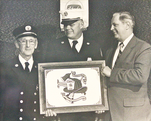 Harold 'Smokey' Schaefer (left) with fire chief Bobby Taylor (center) as he was presented with the 1979 Fireman of the Year award. (Riverhead Fire Department courtesy photo)