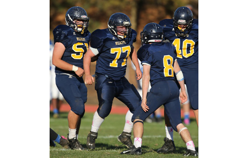 DANIEL DE MATO PHOTO | Shoreham-Wading River's Brennan Gorman (51), Max Goldfarb (77), Chris Rosati (8) and Ethan Wiederkehr (40) celebrate after stopping Elwood/John Glenn on a third-and-one play.
