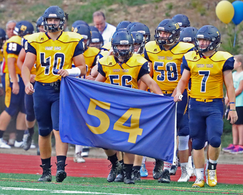 Shoreham-Wading River players Ethan Wiederkehr #40, Logan Snyder #56 and Kevin Cutinella #7 carry the #54 Thomas Cutinella banner onto the field prior to the start of their game against Center Moriches at Shoreham-Wading River High School on September 9, 2016.