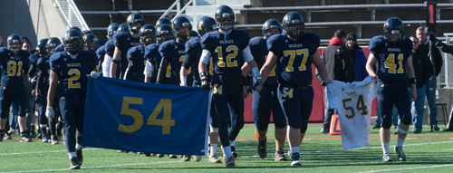The late Tom Cutinella's retired No. 54 jersey held a prominent place as the Shoreham-Wading River players marched onto the field before the game. (Credit: Robert O'Rourk)
