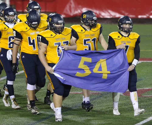 James Puckey, left, and Kevin Cutinella carry the 54 flag in memory of Tom Cutinella onto the field before Shoreham-Wading River's win over Elwood/John Glenn in the Suffolk County Division IV final. (Credit: Daniel De Mato, file)