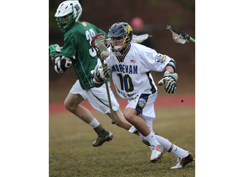 Steve Wiendler, carrying the ball forward, collected 10 ground balls and an assist for Shoreham-Wading River in its season-opening win over Harborfields. (Credit: Garret Meade)