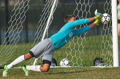 GARRET MEADE PHOTO | Shoreham-Wading River goalkeeper Adam Piotrowski pushing aside a penalty kick by Southold's Will Richter.