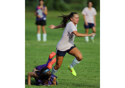 Shoreham-Wading River's Megan Kelly leaves a Port Jefferson defender in her wake as she moves the ball up the field. (Credit: Daniel De Mato)