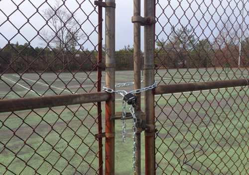 The Shoreham-Wading River High School tennis courts have been closed and locked since March after they were declared unsafe. (Credit: Joe Werkmeister)