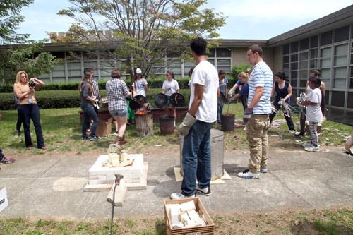 Students placing their art work in a container filled with burning paper.