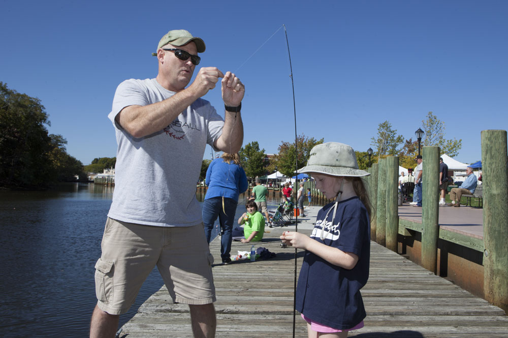 Tom Hubbard of Wading River baits a hook for daughter Ryann, 7.