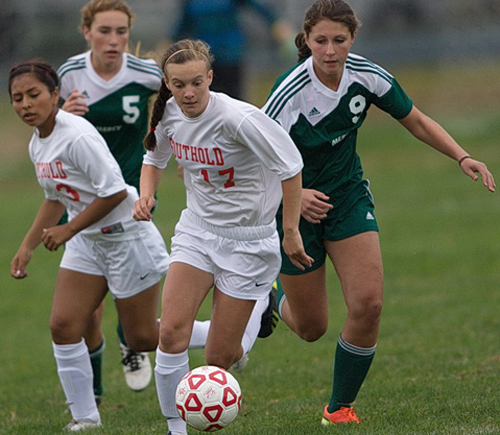Southold/Greenport's Raeanne Berry dribbling forward while being followed by teammate Jasmine Fell and Bishop McGann-Mercy's Madeleine Joinnides (5) and Alexandra Hulse (9). (Credit: Garret Meade)