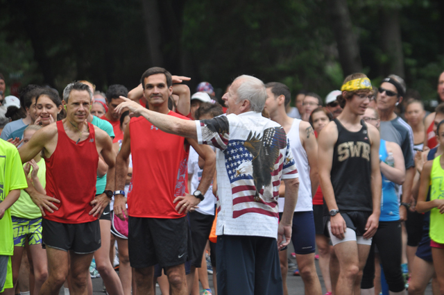 Coach Szymanski entertains the runners before the start of the 2015 SWR July 4 5K race. (Credit: Joe Werkmeister)
