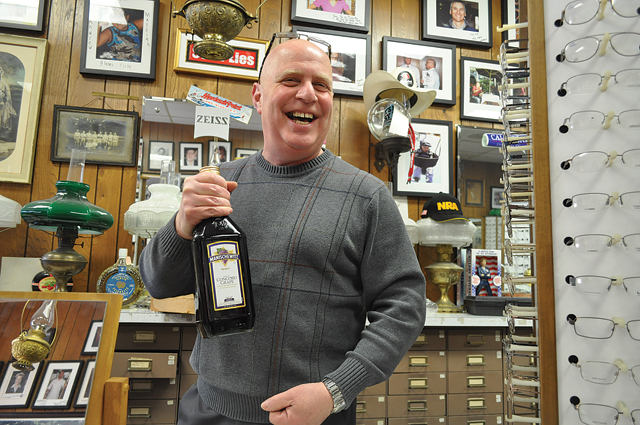 Allied Optical Plan owner Jerry Steiner shows a customer a bottle of Manischewitz wine he received as a gift for passover. (Credit: Grant Parpan)