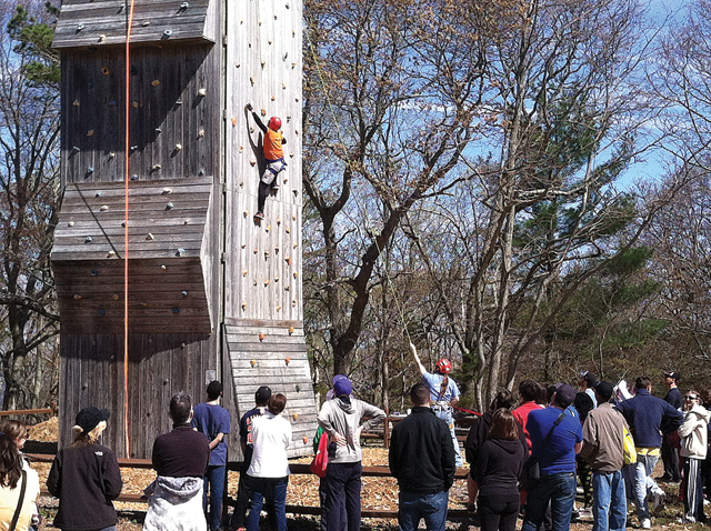NYIT Vocational Independence Program students watch as their dean, Ernst VanBergeijk, scales a rock wall at the Baiting Hollow Scout Camp Friday. (Credit: Michael White)