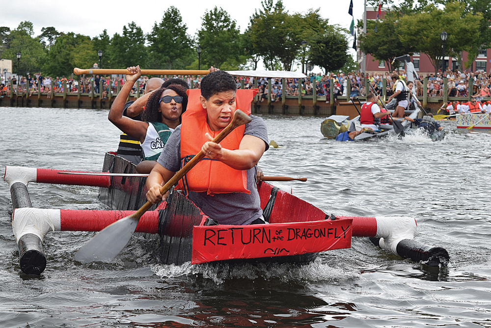 "Deawna Harris (back) and Kerri Harris of Dover, Delaware and their team ""Return of the Dragonfly"" take first place in their heat at the Cardboard Boat Race. (Credit: Vera Chinese)"