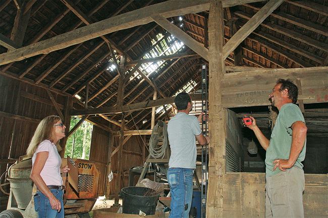 The Kaisers check measurements near the barn's cow box. The elder Mr. Kaiser said he's waiting for the arrival of custom beams that will be used to reinforce the building's structure. (Credit: Barbaraellen Koch)