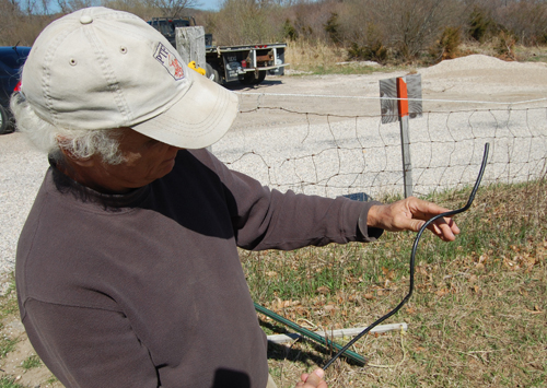Albert Bengolea holds up one of the fence wires that was cut on the 4-H property. (Credit: Grant Parpan)