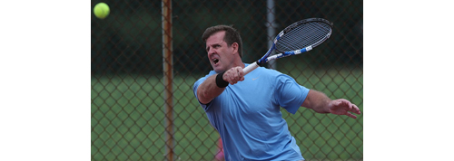 Kieran Corcoran returning a shot Sunday when he and Chris Ujkic won their eighth straight men's doubles title in the Bob Wall Memorial Tournament. (Credit: Garret Meade)