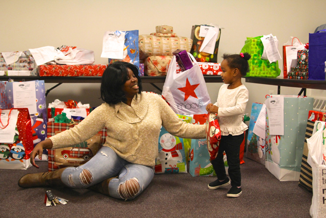 The Butterfly Effect Project founder Tijuana Fulford and Taliah, 2, organize Christmas gifts donated by Teachers Federal Credit Union.