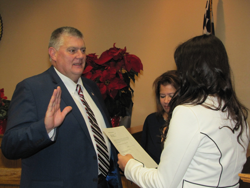 Councilman Tim Hubbard is sworn into office Friday by his daughter, Meaghan Howard.