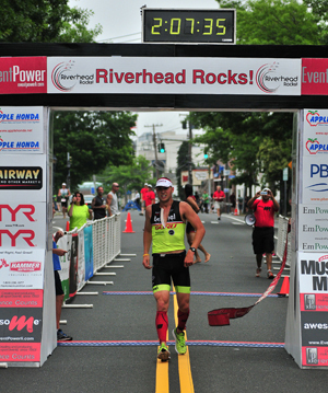 BILL LANDON PHOTO | Riverhead Rocks triathlon winner Tim Steiskal of Brookhaven as he crosses the finish line.