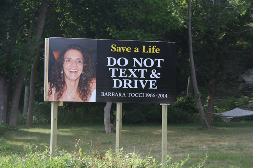 A sign on Route 24 warns drivers of the dangers of texting and driving following the death of Barbara Tocci on the road earlier this year. (Credit: Carrie Miller)