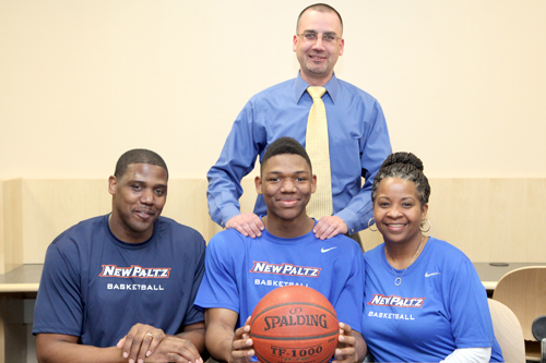 Brandon Tolliver is pictured with his mother and father Shanneikqua and Bill Tolliver with Varsity Basketball Coach John Rossetti.