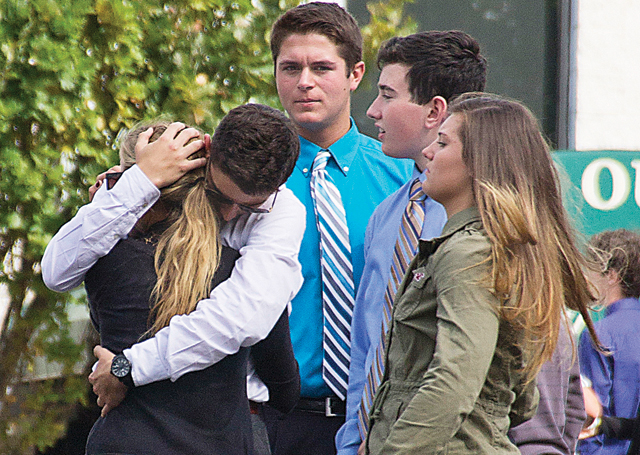 Friends embrace outside the funeral, where more than a thousand attendees paid their respects to Tom Cutinella. (Credit: Paul Squire, file)
