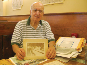 Tony Meras holds up a picture of family members working in the diner decades ago. (Credit: Nicole Smith)