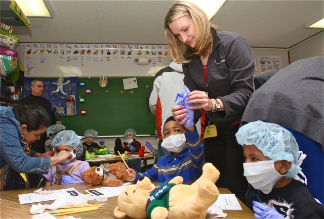 Ms. Ladowski helps Jaiveon Lee put on protective medical gear before examining his teddy bear, Nick.