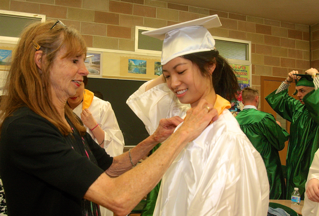 Mercy teacher Patricia Doroski helps Suren Gu of Southampton with her gown. (Credit: Barbaraellen Koch)