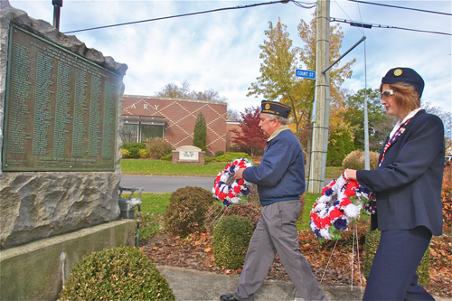 American Legion commander Mike Pankowski and Ladies Auxillary vice president Darlene Folkes place the wreaths at the War Memorial Monday morning.