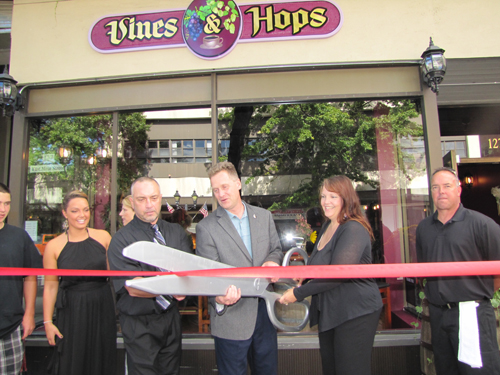 TIM GANNON PHOTO | Riverhead Supervisor Sean Walter is flanked by Jeff and Christine McKay is celebrating the opening of their new venture, Vines & Hops, in downtown Riverhead Sunday.