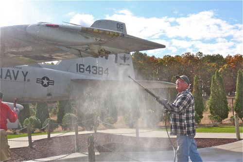BARBARAELLEN KOCH PHOTO | Volunteer Paul Dooling, of Farmingdale, power washes the A-6E.