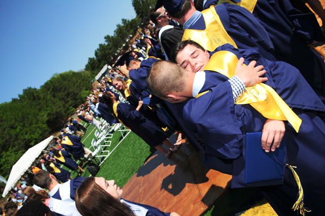 Two graduates embrace. (Credit: Bill Landon)