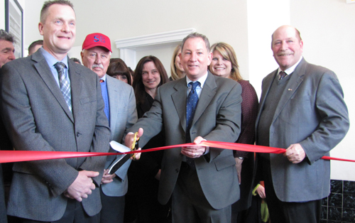 Michael Butler (center) cuts the ribbon Thursday at the E. Main St. apartment complex. (Credit: Tim Gannon)