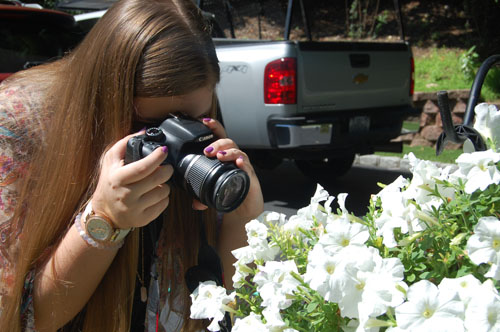 Amanda de Lauzon takes a picture of flowers. She's had several still images featured on Jones Soda bottles. (Credit: Nicole Smith)