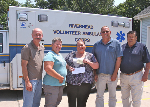 BARBARELLEN KOCH PHOTO | Riverhead Volunteer Ambulance Corp board president Kim Porkorny (center) and vice president Joe Sokoloski (far left) accepted donation s from 'Heidi's Helping Angels' honoree members (from left) June and John Behr and president Jim Stark Tuesday afternoon.