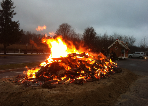 TIM GANNON PHOTO | Thousands of pieces of wood keep the annual bonfire roaring in downtown Riverhead.
