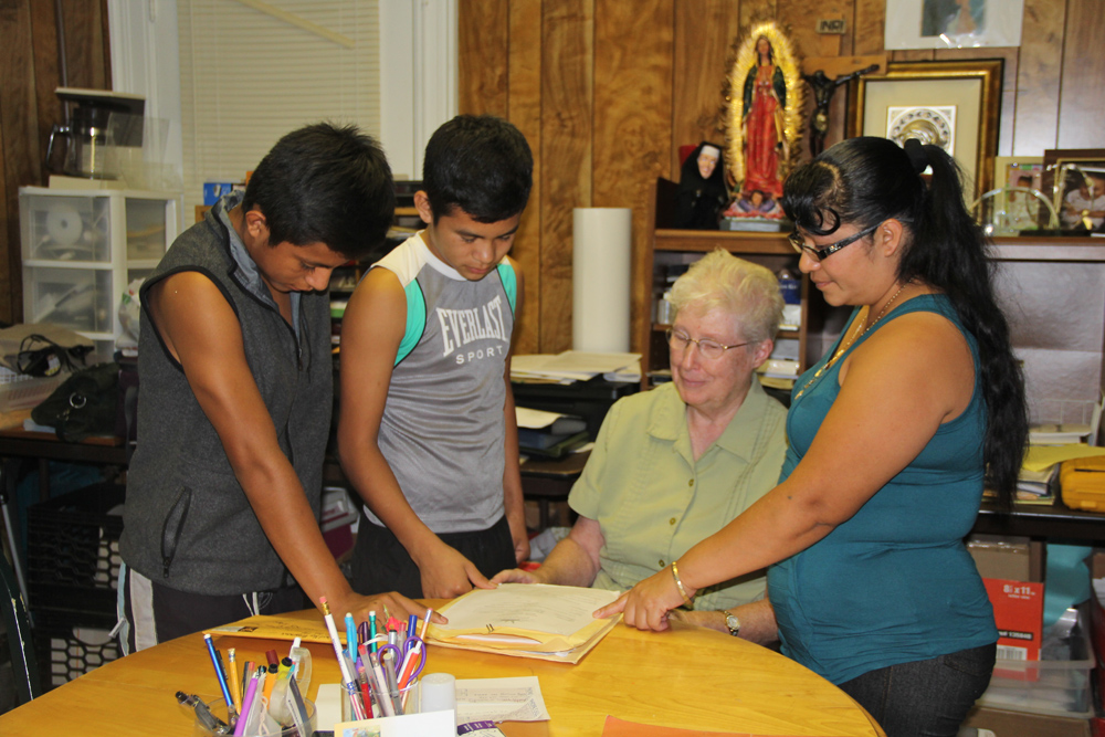 Sister Margaret Smyth of the North Fork Spanish Apostolate (center) with Estabon, 16, and Pedro, 14, and their mother Marta in July. (Credit: Carrie Miller, file)