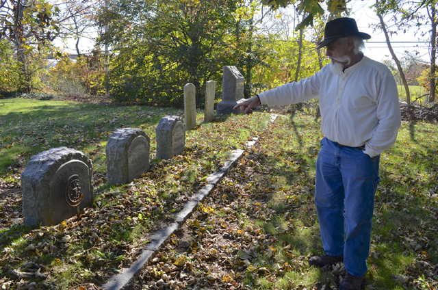 Bill Meyer points out dates on gravestones in the church's cemetery.