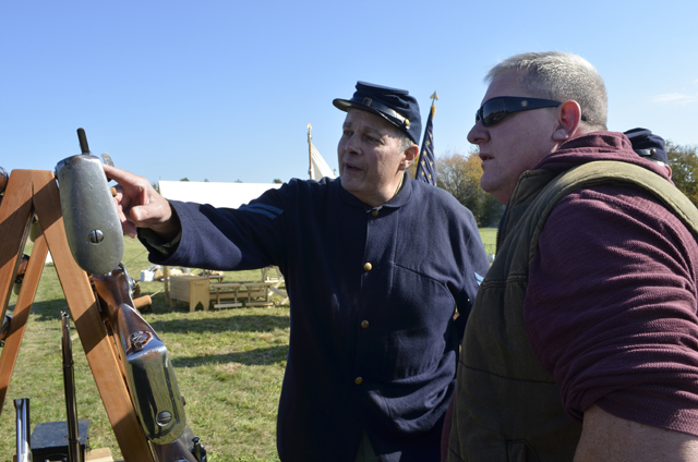 Dave Courtenay of  the 67th New York Volunteer Infantry's Company K talks rifles with Steve Thompson of Baiting  Hollow.