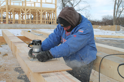 PAUL SQUIRE PHOTO | Erek Berntsen cuts wood at a construction site near the Glass Greenhouse in Jamesport.