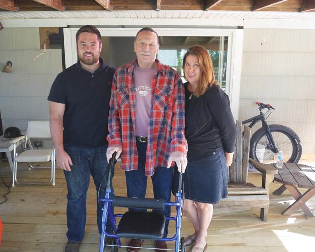 Bill (center) and Nancy Esposito with their son, Bill at home in Peconic. The family is on the back deck that was built for Mr. Esposito after he was injured in March (Credit: Krysten Massa)