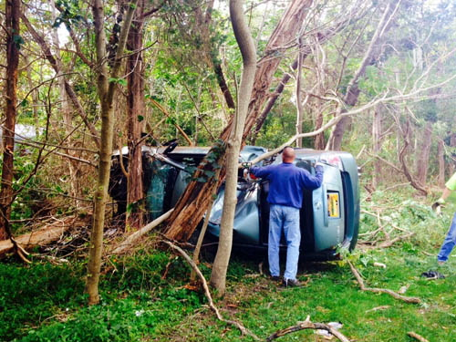 RACHEL YOUNG PHOTO | Tree branches around a Nissan Altima had to be cleared on Monday to get it out of the woods.