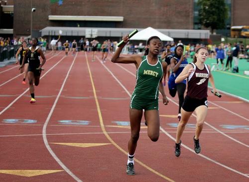 McGann-Mercy senior Danisha Carter crosses the finish line first heat of the 4 x 100 relay. (Credit: Hal Henty)