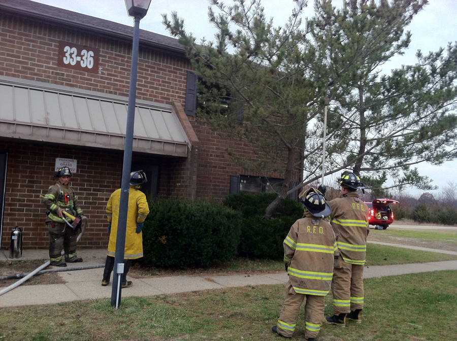 Riverhead firefighters breaking windows in an upper floor window at the Doctors Path Apartments Monday afternoon. (Credit: Michael White)