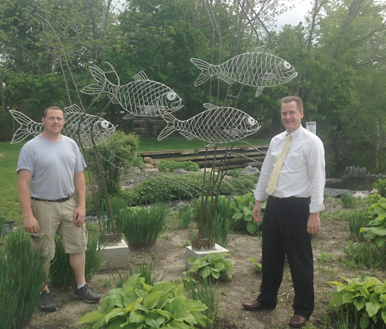Long Island Aquarium Exhibit Artist Eli Fishman shows Riverhead Town Supervisor Sean Walter one of two steel fish sculptures that mark a fish ladder at Grangebel Park. (Courtesy photo)
