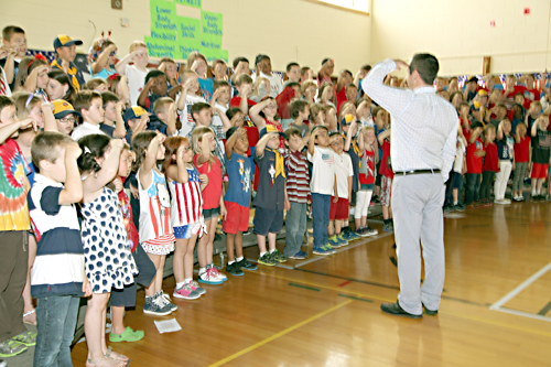 Riley Avenue second-graders, under the direction of music teacher Keith Maguire, sang patriotic songs Friday in salute to the American flag. (Credit: Sandra Kolbo/Riverhead School District)